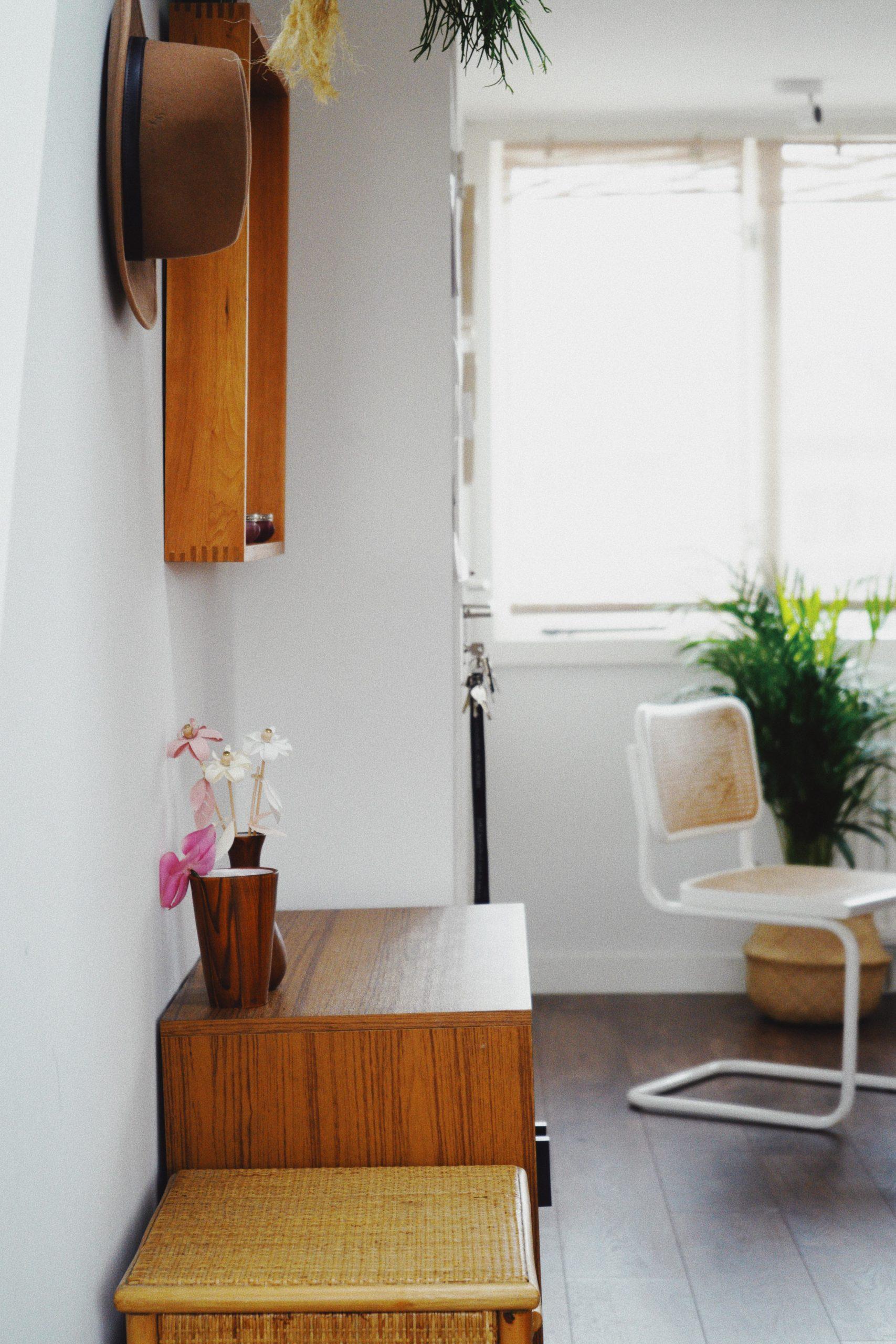 holzschrank und spiegel vor weißer wand im Hintergrund Stuhl und pflanze