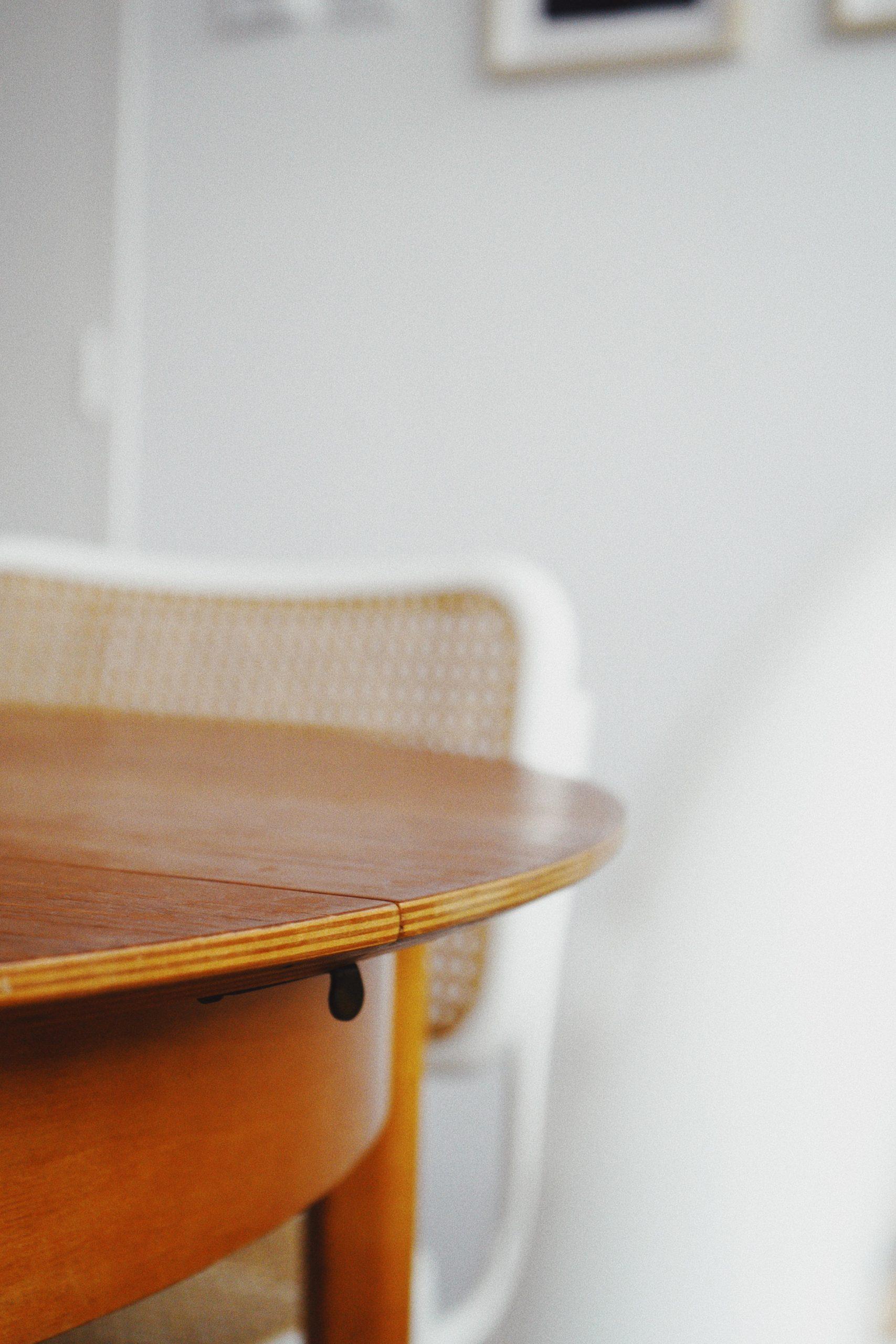 Holztisch und Stuhl vor weißer wand