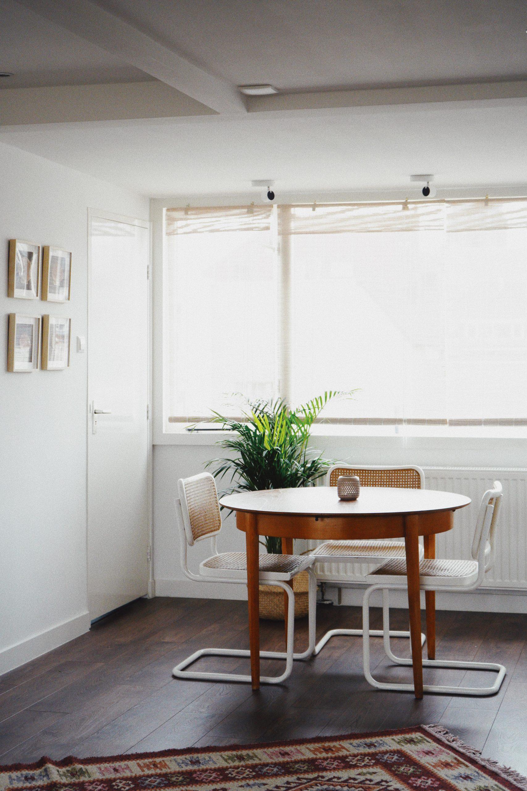 holztisch mit Stühlen und pflanze vor Fenster