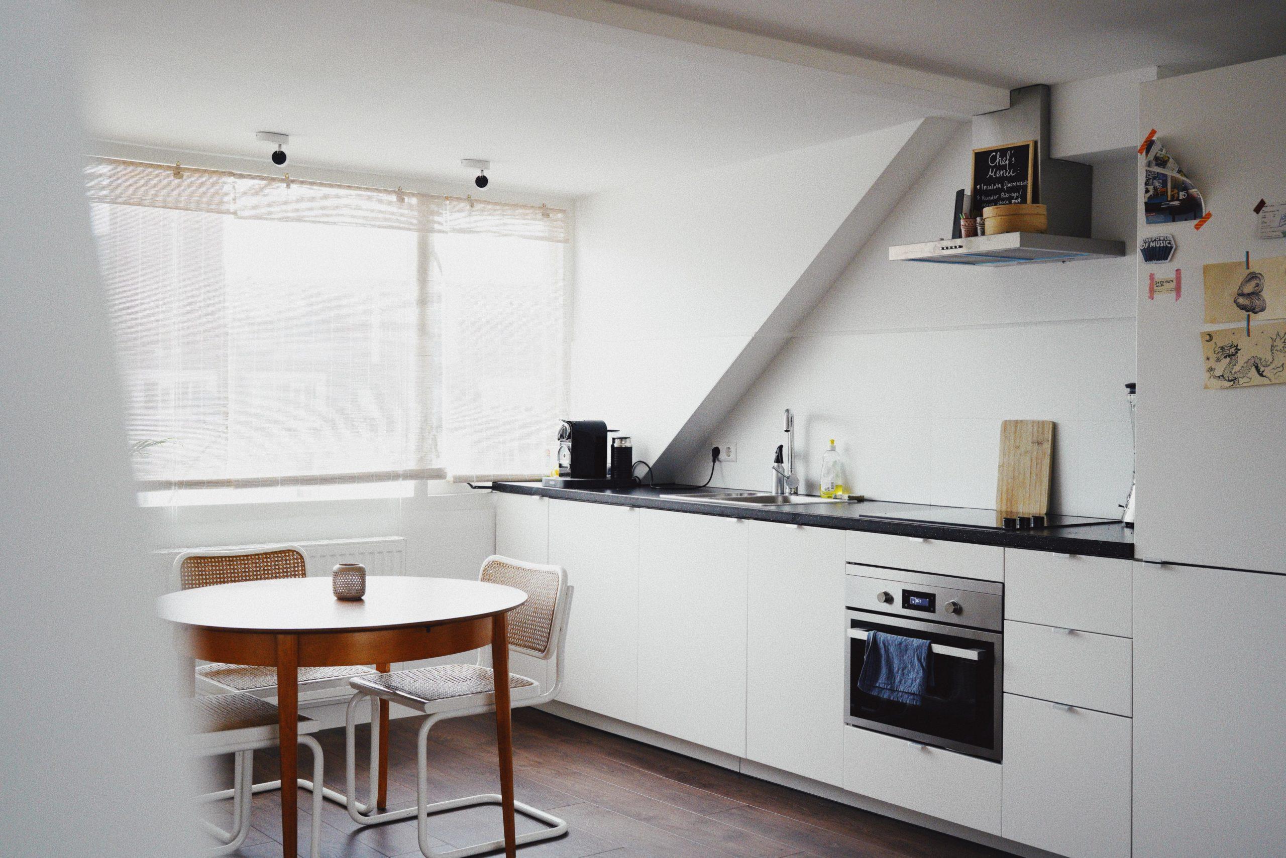 holztisch mit stühlen vor Küchenzeile und Fenster