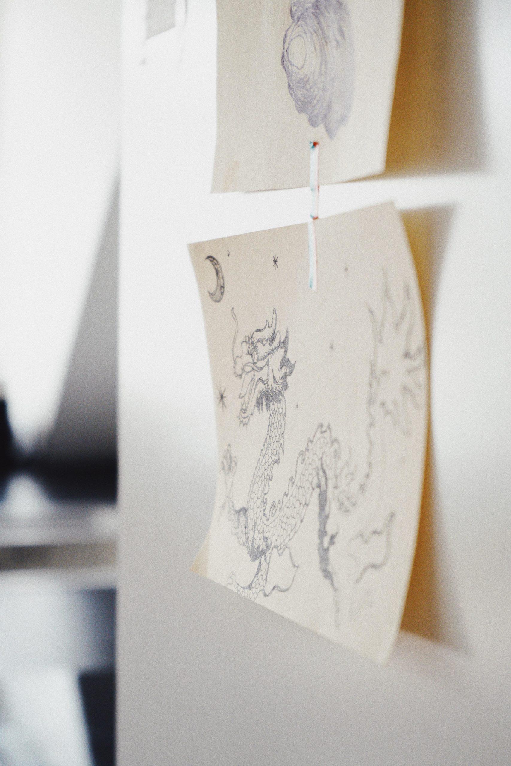 Blatt mit Skizze von Drachen auf schrank geklebt