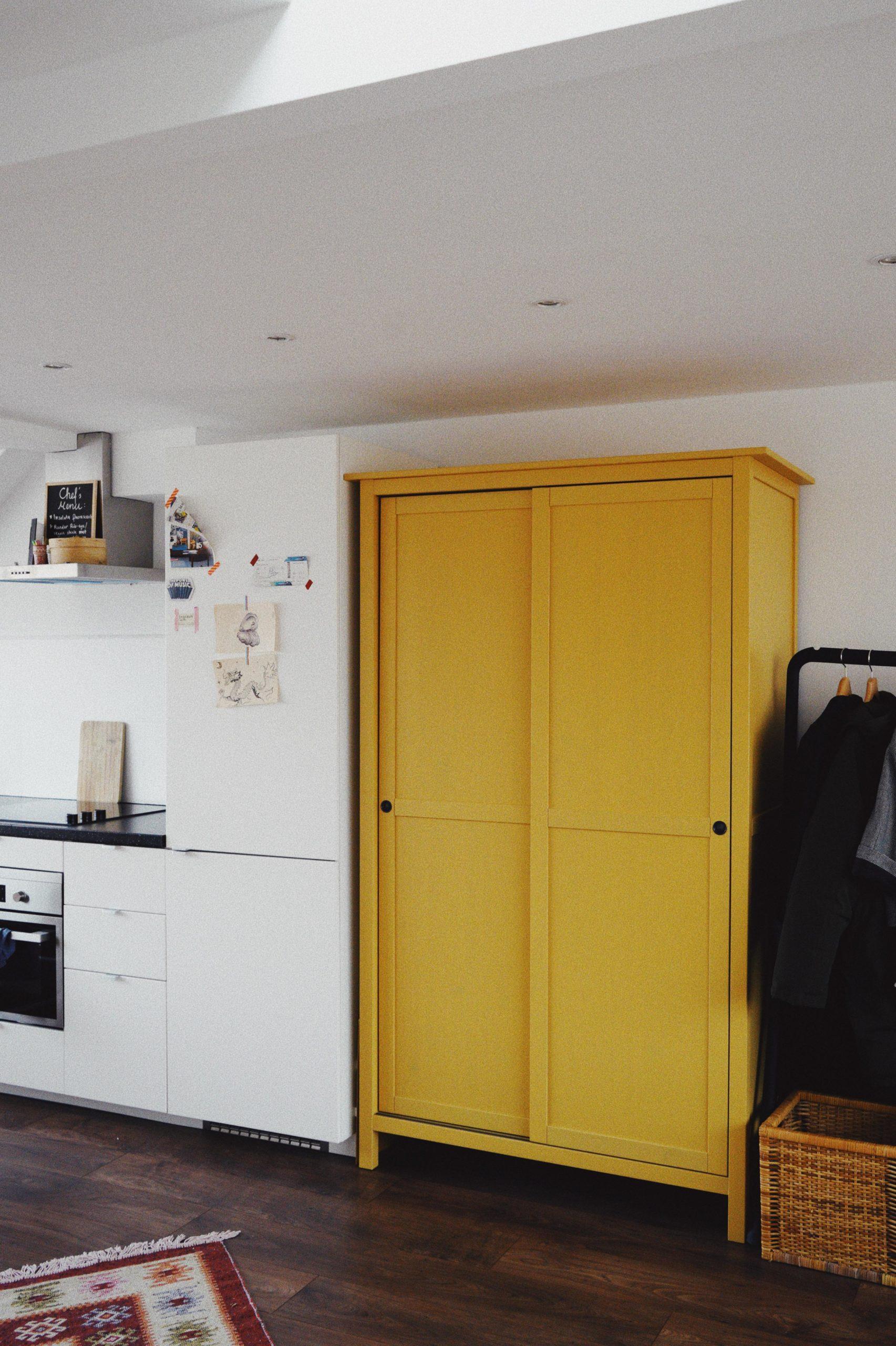 gelber schrank zwischen Küchenzeile und Kleiderstange