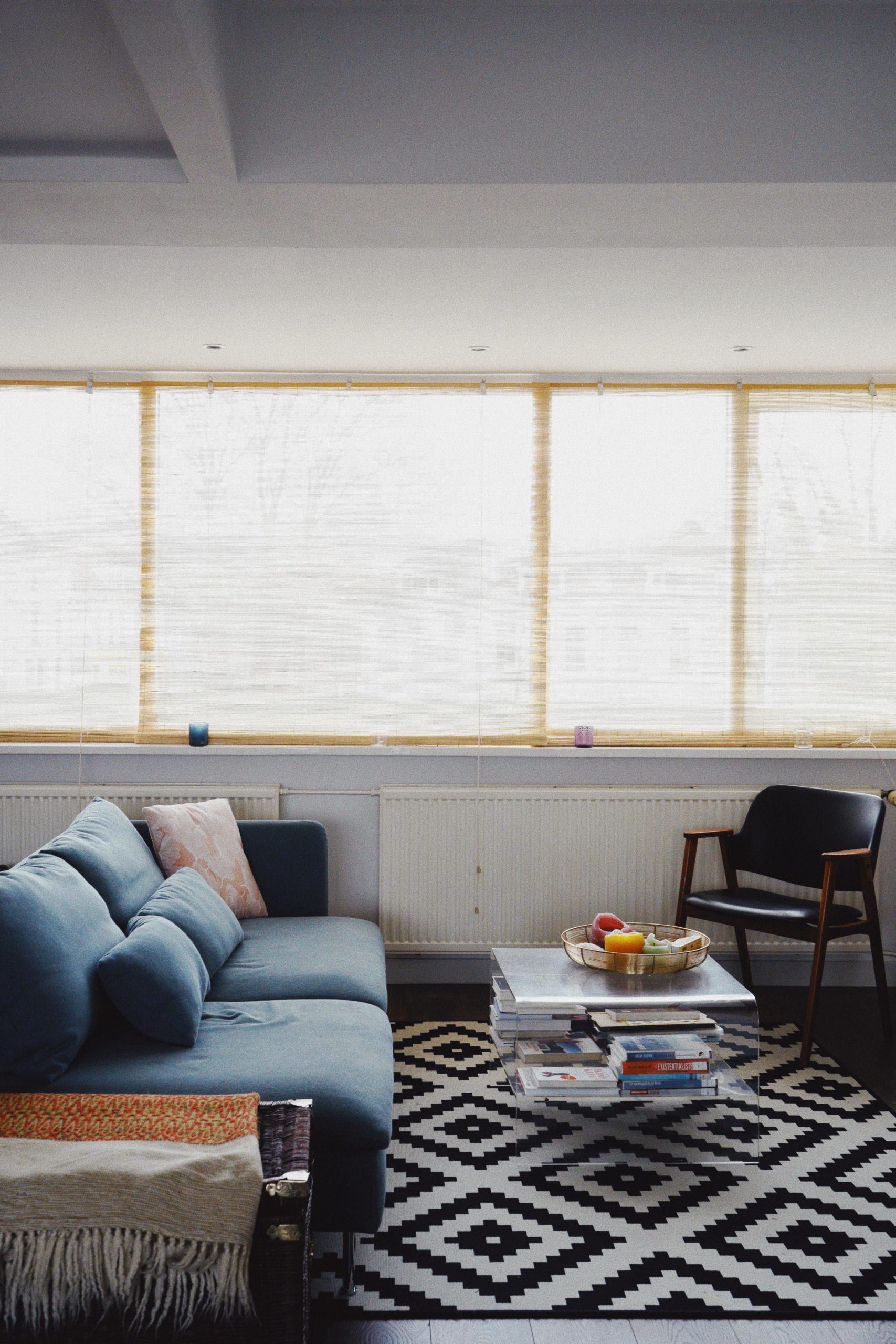 Türkises sofa plexiglastisch und Sessel vor Fenster