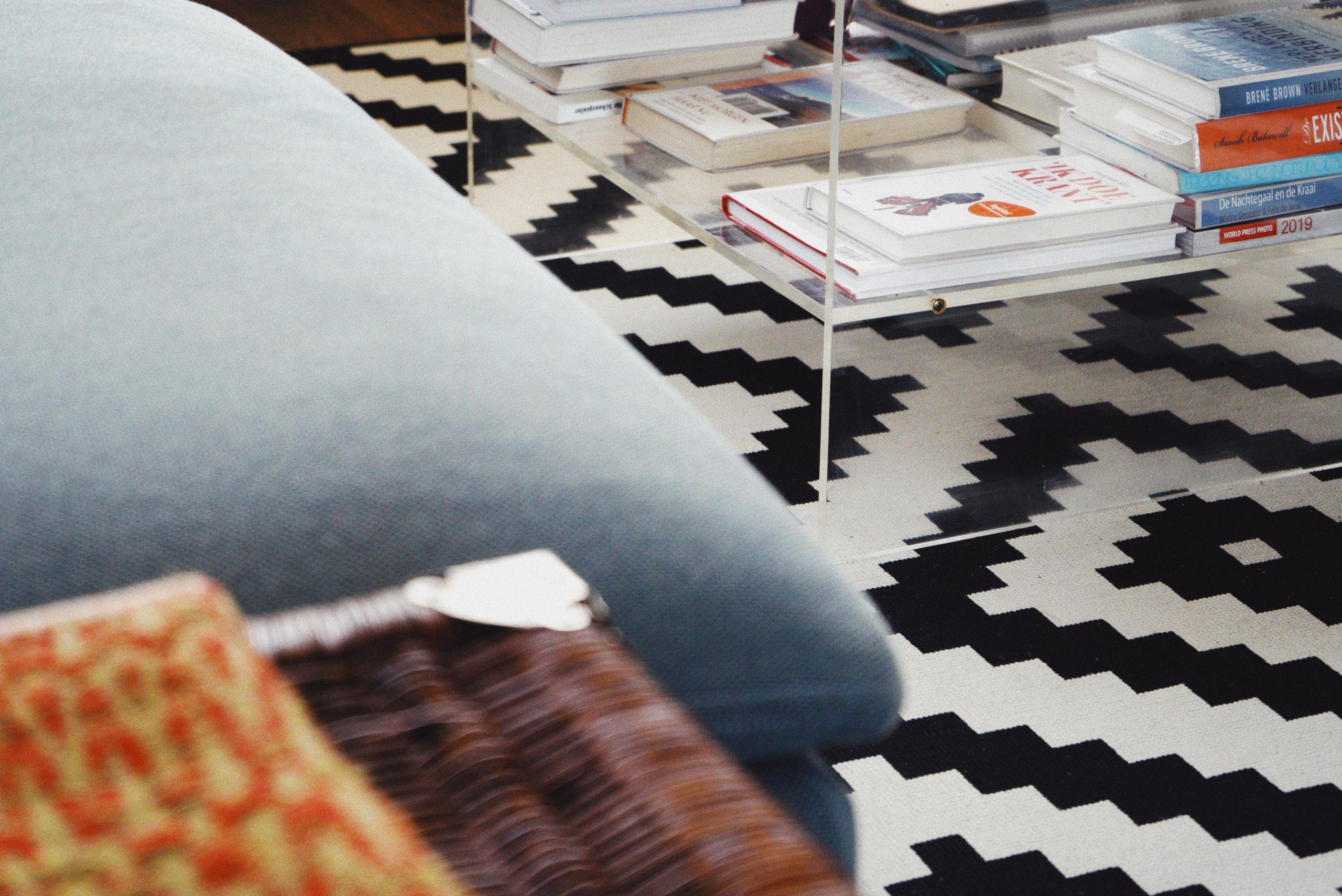 türkises sofa vor plexiglastisch mit Büchern