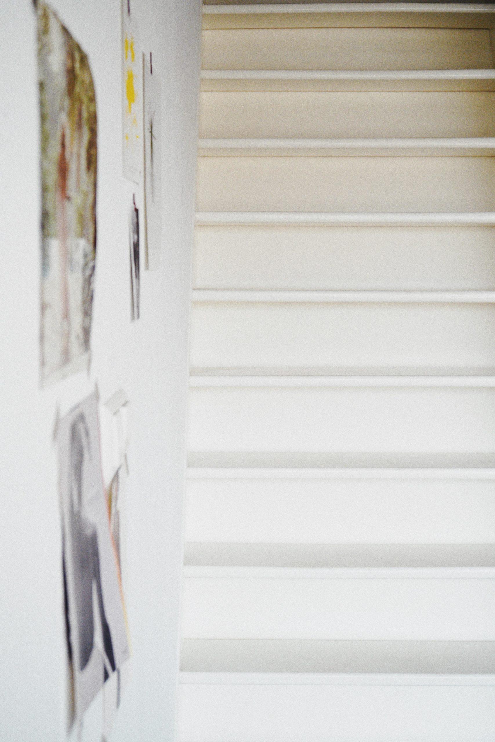 weiße Treppe neben wand mit Fotos
