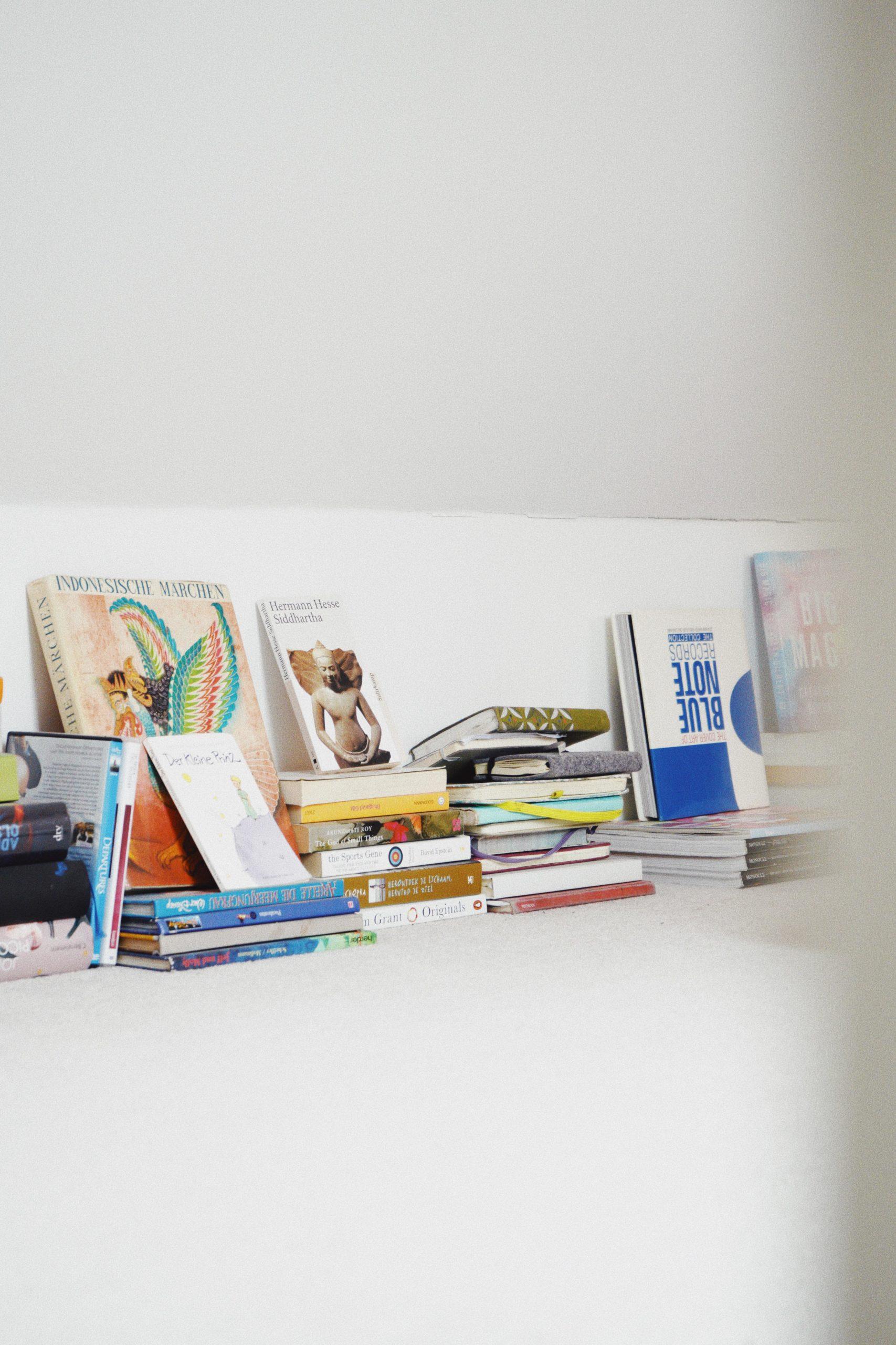 Bücherstapel auf Teppichboden vor weißer wand