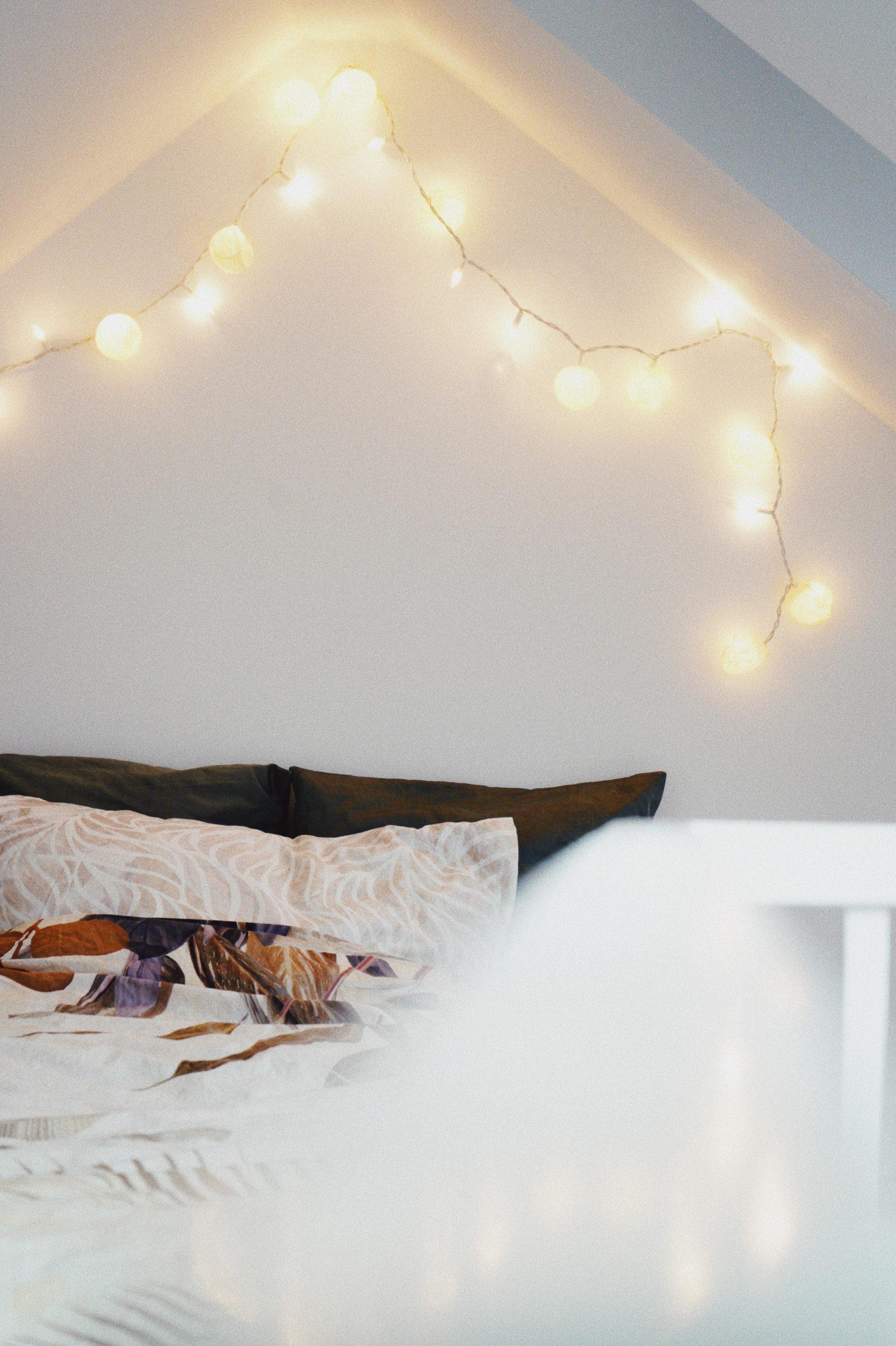 Bett und Lichterkette vor weißer wand